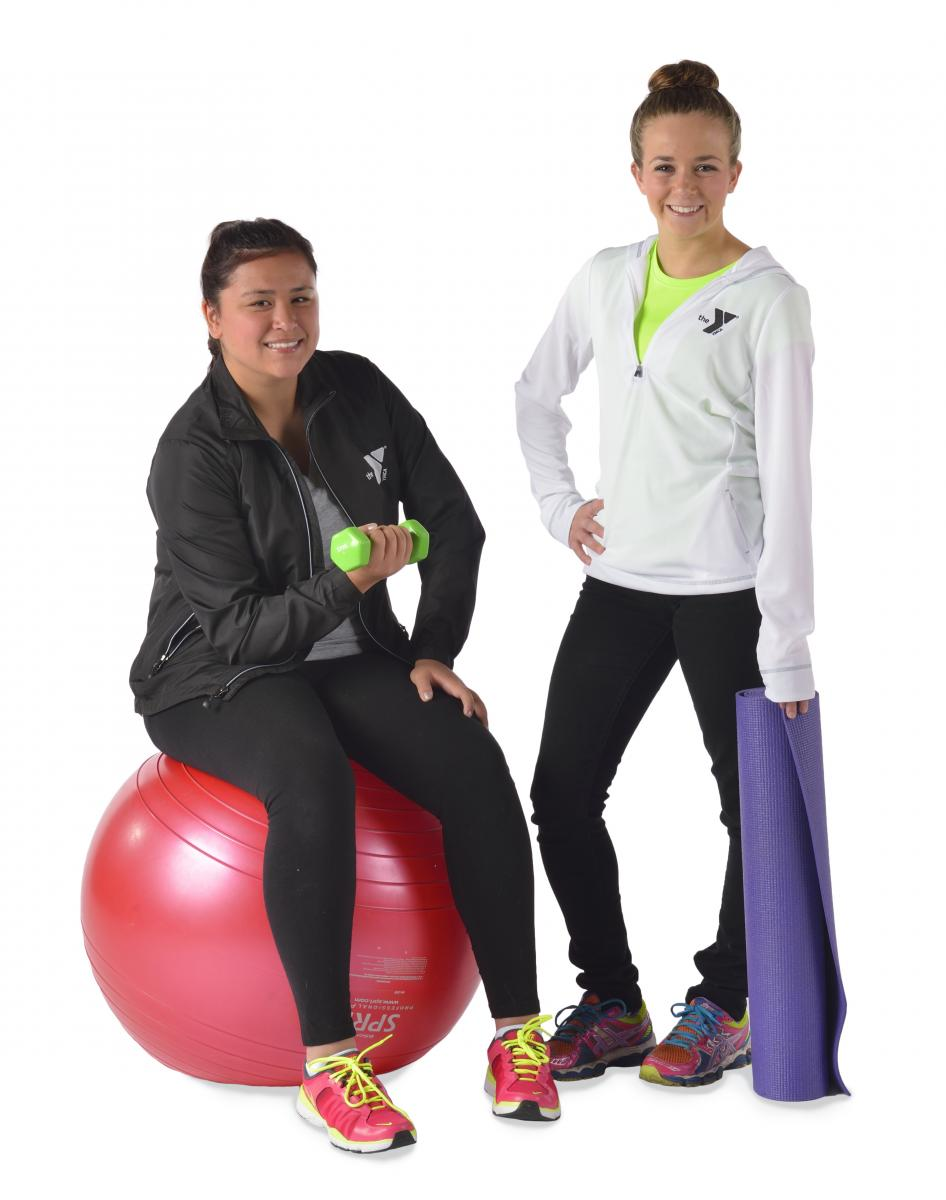 Two women posing with a yoga ball and yoga mat.
