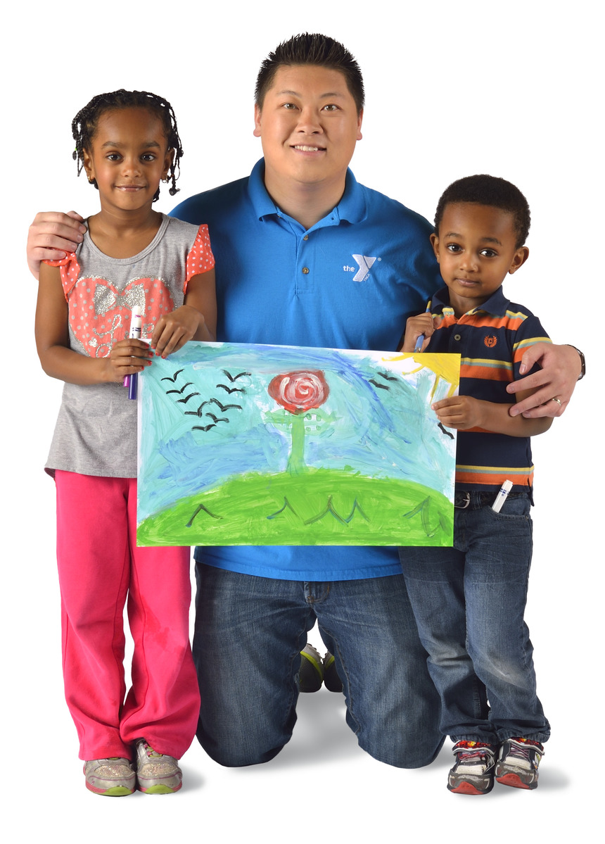 Staff member holding up a picture with two children.