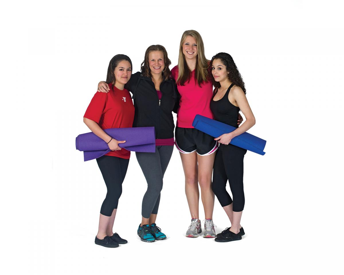 Four girls with rolled up workout mats.