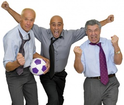 Three men in dress clothes with a soccer ball who are very excited about the Corporate Programs at the YMCA.