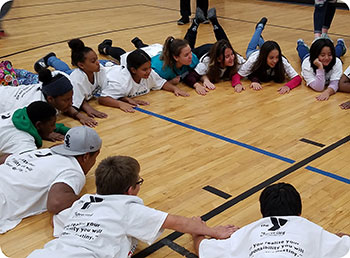 Large group of students playing a game in a circle on the gym floor.