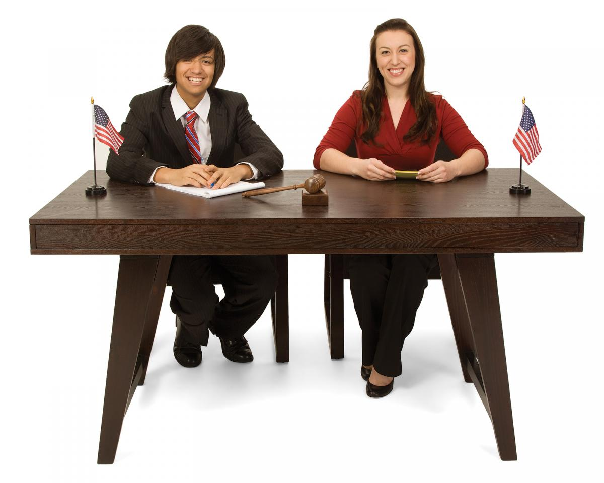 Teen girl and teen boy sitting at a desk for a mock trial.