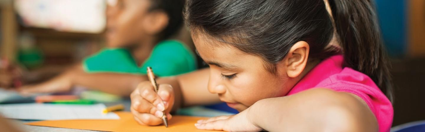 Girl coloring with crayon at desk