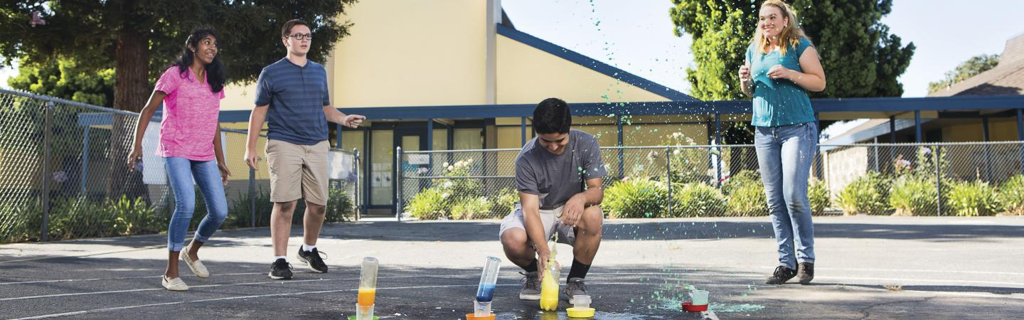Teens performing science experiment outside.