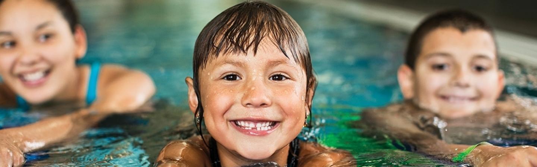 Three children in an aquatics pool smiling for camera.