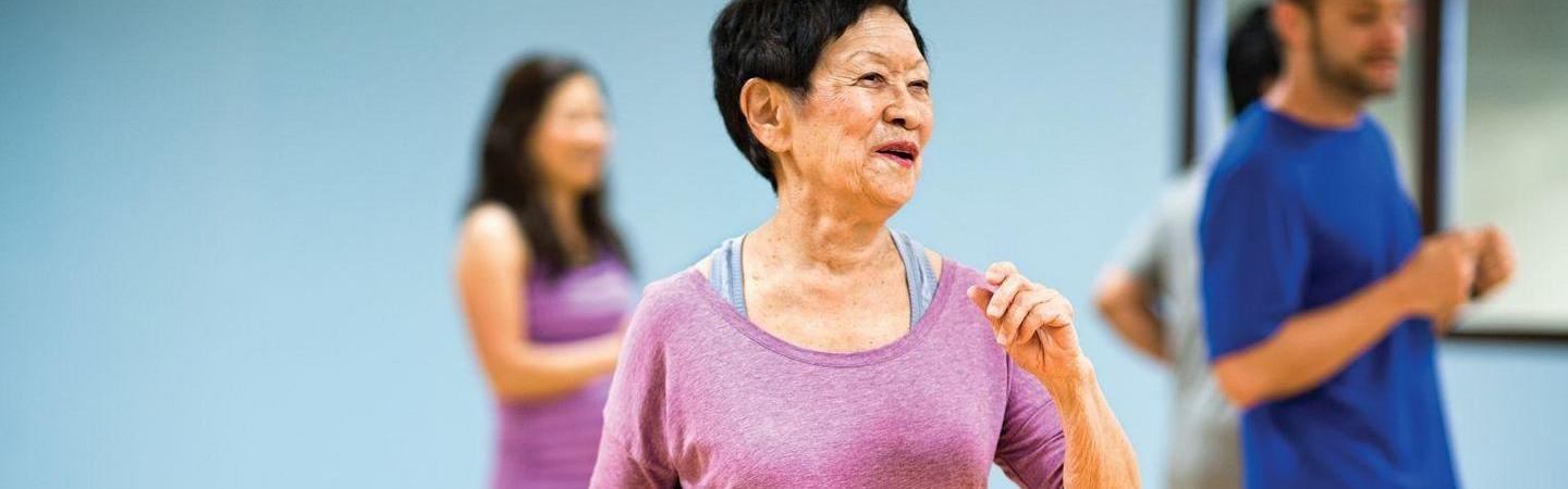 Group of active older adults working out in a class.