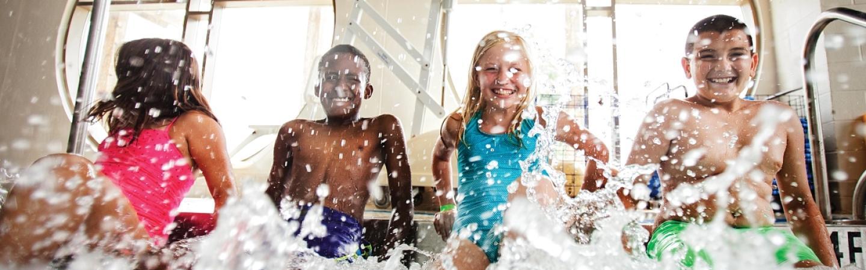 Four children splashing water on edge of pool.