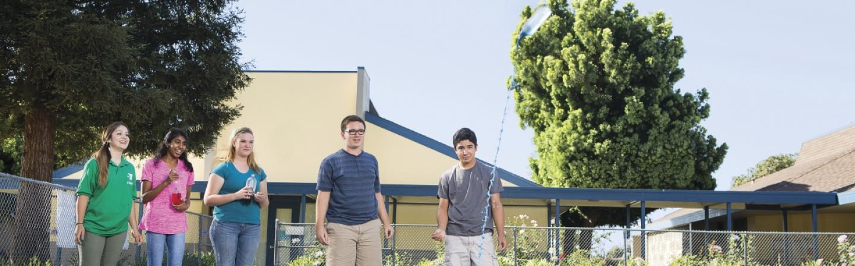 Four teenagers watching water rocket launch.
