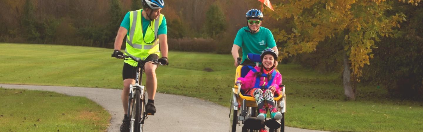 A special adaptive duet bike on a bike path accompanied by another ride.