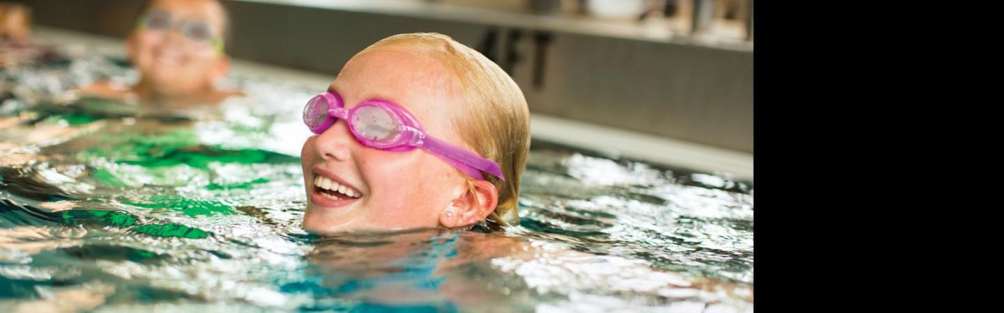 Girl with goggles on swimming in a pool.