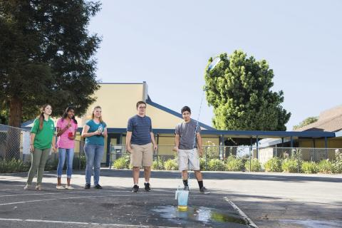Four teenagers watching water rocket launch.