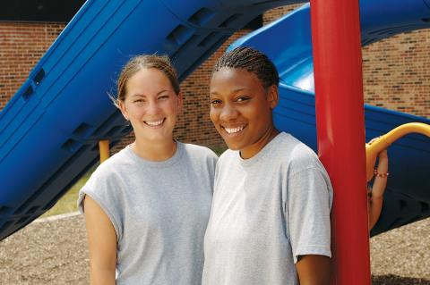 Two girls in front of slide.